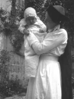 Baby Boy in a Long White Dress Being Held by His Nurse